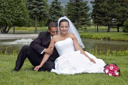 Just married multi ethnic couple sitting in the grass