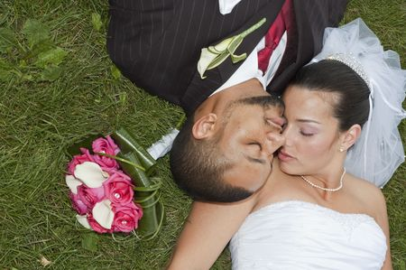 Just married multi ethnic couple laying in the grass photo