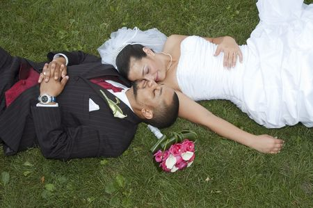 Just married multi ethnic couple laying in the grass