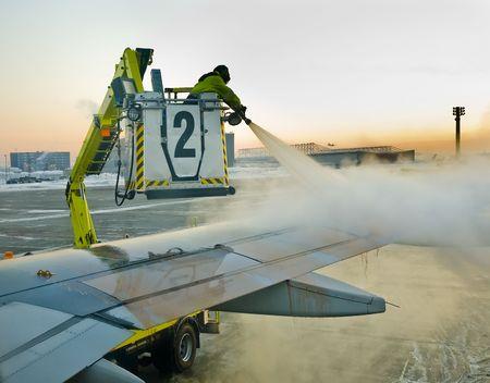 早朝に出発する前に解凍の飛行機の翼を男します。