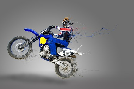 Man riding his motocross bike with paint detaching all over his bike and body photo