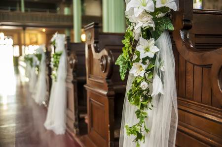 Wedding decoration white flowers and green leafs hanging on the church benches
