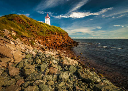 Eroded beach cliff and lighthouse Prince Edward Island Canada Stock fotó