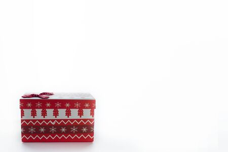 A red Christmas box with gifts and a bow stands on a white background with place for postcard text with a left. On the box are Christmas trees and snowflakes. Stock Photo
