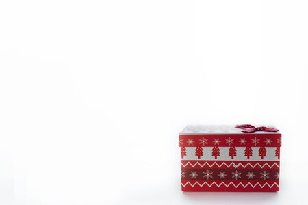 A red Christmas box with gifts and a bow stands on a white background with a place for a postcard text from the right. On the box are Christmas trees and snowflakes. Banque d'images