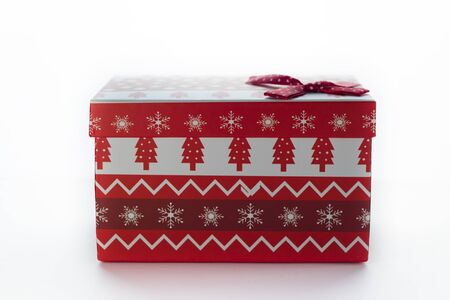 Christmas box with red gifts on white isolated background with the image of Christmas trees located sideways. There is a bow in the corner Stock Photo