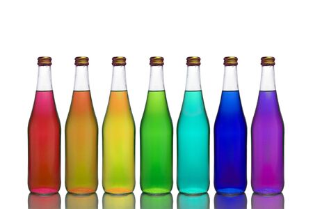 Transparent glass bottles of different colors stand on a mirror surface on a white background making up an owl rainbow.