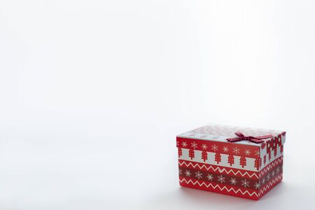 A red Christmas box with gifts and a bow stands on a white background. Stock Photo
