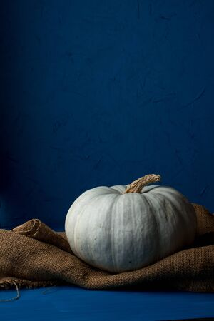 Still life of light pumpkin lies on a rough brown bag for vegetables on a blue background side view.