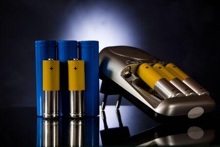 Akkus unterschiedlicher Größe neben dem Ladegerät auf einem schwarzen