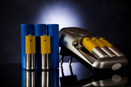 Batteries of different sizes next to the charger on a black
