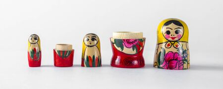 Three wooden nesting dolls demonstrate the continuity of generations on a light isolated background.