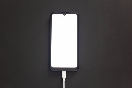 The phone on a black background with a luminous screen is charging.