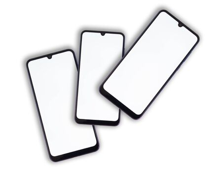 Three smartphones lie on one another with a white display on a light isolated background. Imagens