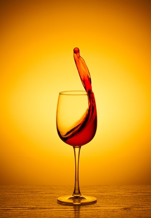 tred: Red wine on tRed wine in a glass with a splash on the table with a backgroundhe background Stock Photo