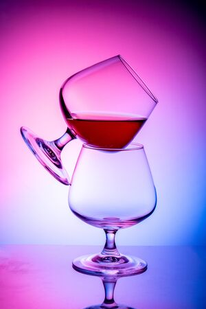 Two glass glasses on a colored background