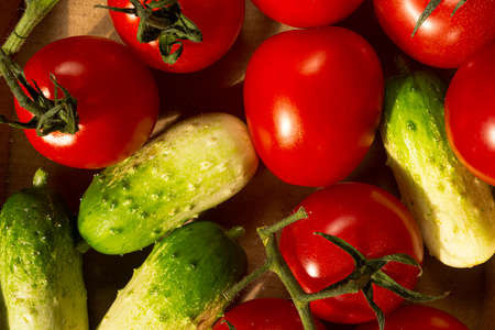 food-backgrounders, mini cucumbers and tomatoes on a branch Фото со стока
