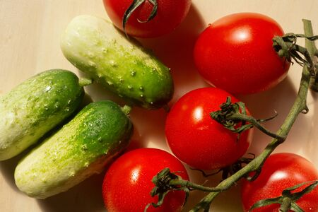 food-backgrounders, mini cucumbers and tomatoes on a branch Stock Photo