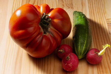 large red tomato cucumber and radish on a wooden background