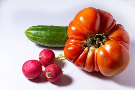large red tomato cucumber and radish on a white background Фото со стока