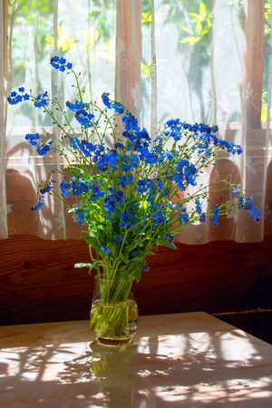 A small bouquet of blue forget me nots in a vase in the sunlight
