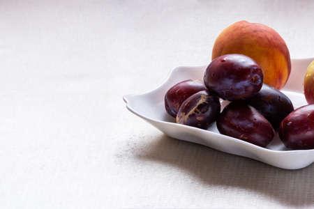 Apple peach plum on a white platter