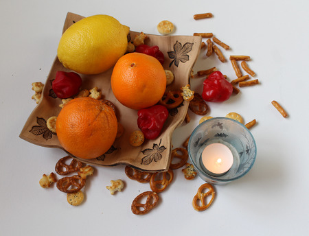 Fruit and salt sticks arranged on a table with a candle