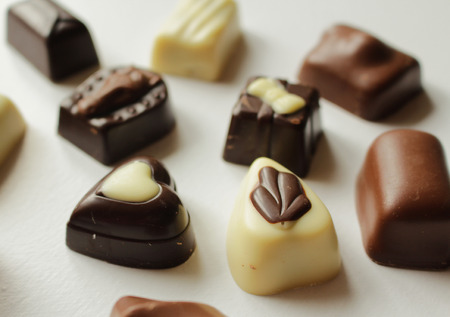 Pralines - Delicatessen - Sweets made of black, milk and white chocolate Stock Photo