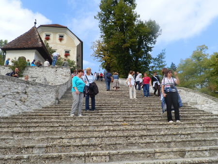 Tourists at stairways leading to a church located on an island in the middle of Bled lake, Slovenia