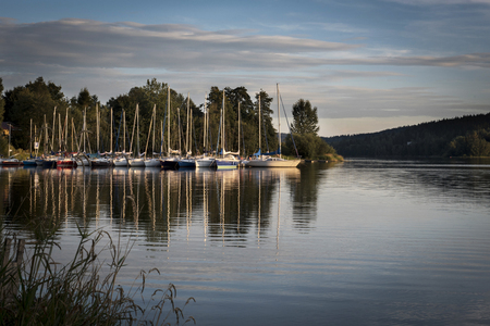 lipno: Harbor of sailboats on the shore of a Lipno Dam reflecting in water at sunset