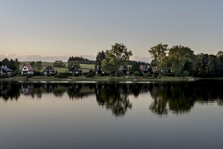 lipno: Small houses on the shore of the Lipno Dam reflecting in the water at sunset around the woods