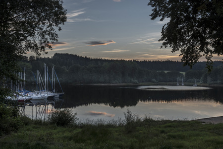 lipno: A sailboat on and the Lipno dam reflecting in the water at sunset around the woods