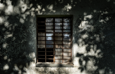 An old rusty window on a haunted shaded wall