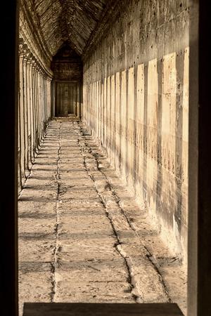 Stone corridor in Angkor Wat temple with sun rays in Cambodia Redakční