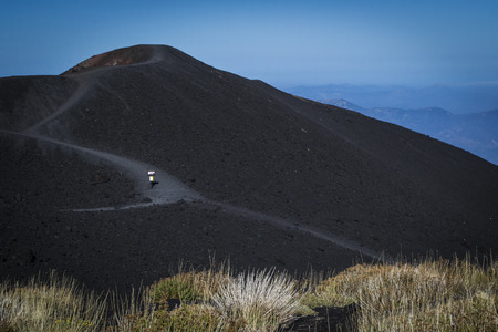 an extinct crater of the Etna volcano with black lava around in Sicily
