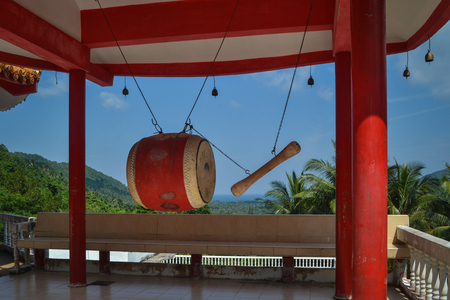 Red big drum with stick hanging on the top of a hill in a golden buddhist temple near a small thailand village 版權商用圖片