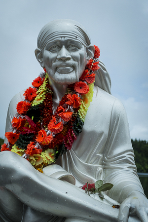 statue of saint in a life size with a floral ring around the neck of Mauritius