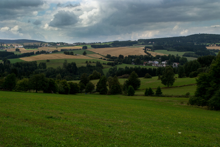 green meadows, yellow fields and forests under the storm clouds in the Bohemian-Moravian Highlands Stock Photo