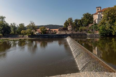 sun-lit weirs on the river Sazava in the background of S?zava monastery building