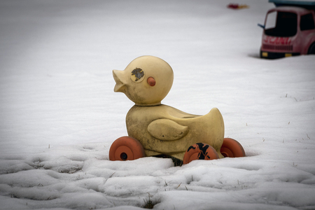 Plastic yellow duck on deserted snowy playground in winter