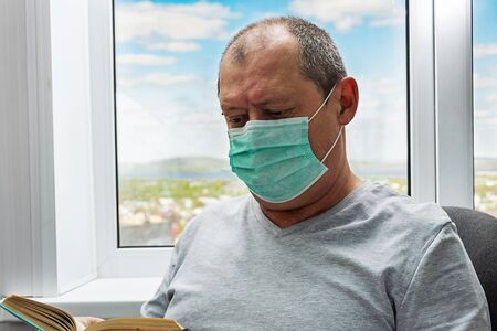 An elderly man in a protective mask reads a book