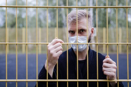 Masked man behind bars on set