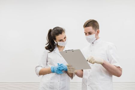 Two doctors talk in protective masks with tablet. Male and female doctors communicate in the medical modern white office. Covid
