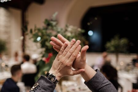 The guest at the banquet applauds. Hands applause. Mens hands applaud.