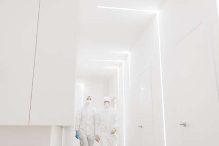 Two doctors in protective suits walk during an epidemic covid in the white corridor of the hospital.