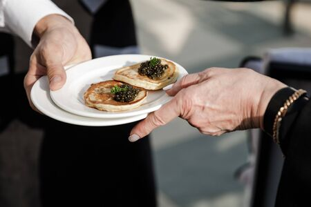 The waiter passes a plate of pancakes and black caviar to the guest.
