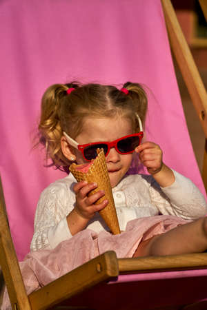 Cool and cute kid. Sunglasses for children. Girl on deck chair with ice cream.