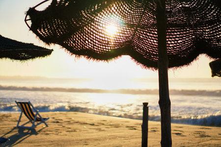 Wooden lounger hotel at sunset under umbrella.