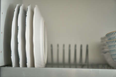 Dishes in the dryer. There are plates in the kitchen. White service. A drawer for dishes.