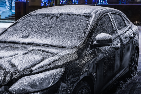 icy conditions: frozen car in the parking lot of the hotel the night winter